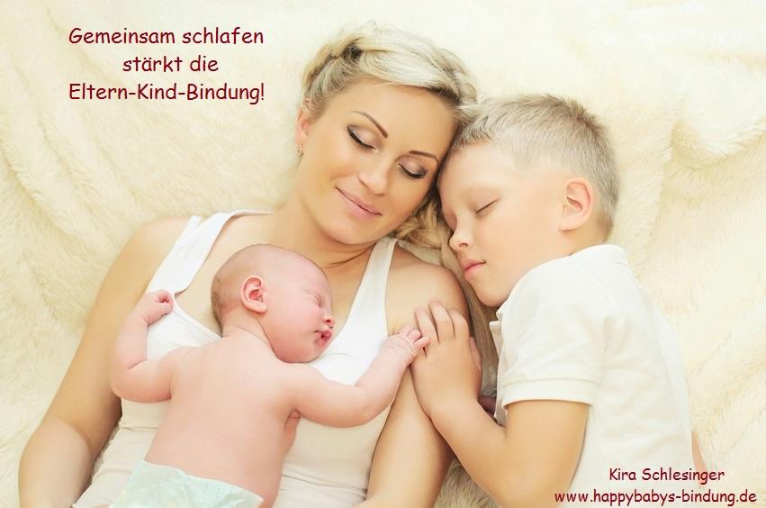 Mutter mit ihren beiden Kindern zusammen im Familienbett