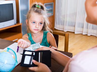 Loben und Belohnungen - Kind erhält Geld für gute Leistung