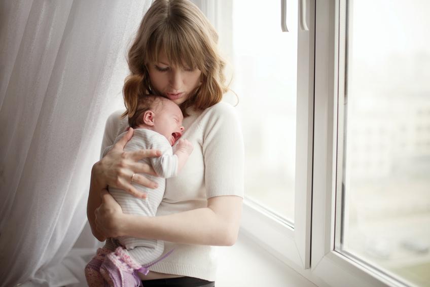 Abendliches Weinen - Junge Mutter und weinendes Baby